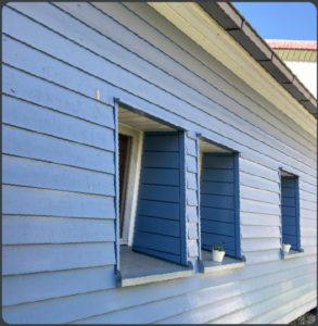 Mit deckender Holzschutzfarbe lackierte Holzfassade.